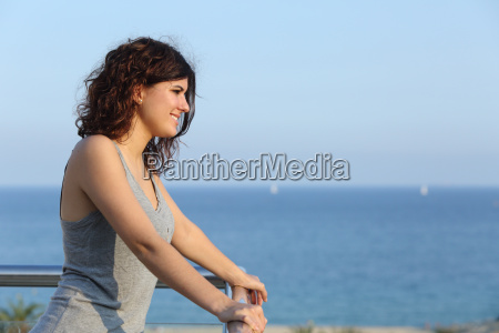 attractive woman watching the sea from