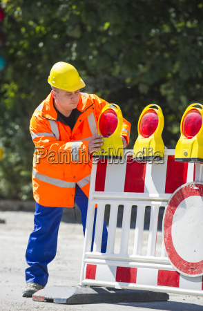 worker checks the construction site barrier