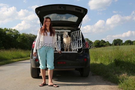 woman and dog on a car