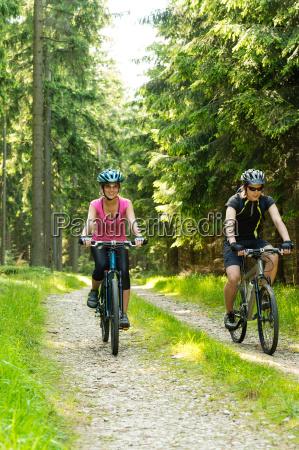 joyful biker couple in woods