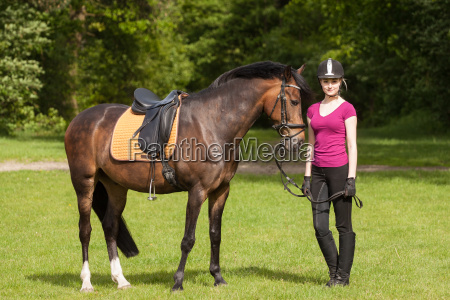 girl stands next to her horse