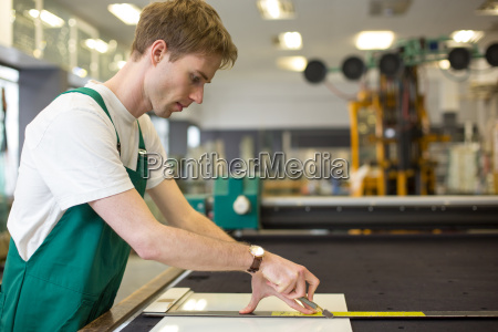 glazier in workshop cutting glass
