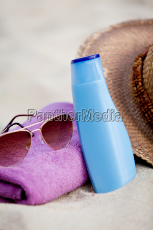sunscreen on holiday straw hat with