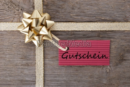golden bow with red tag with