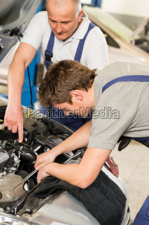 middle aged car repairman helping colleague