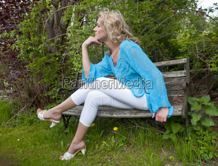 young woman sitting on wooden bench
