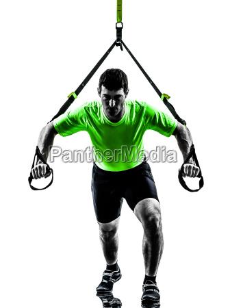 man exercising suspension training trx