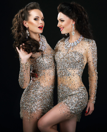excited glamorous couple in platinum dresses