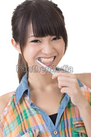 asian woman brushing teeth