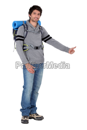 man with backpack hitchhiking