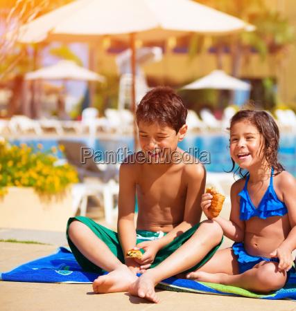 happy kids eating near pool