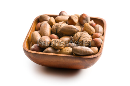 various unpeeled nuts in wooden bowl