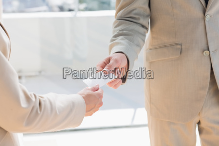 businessman passing card to businesswoman