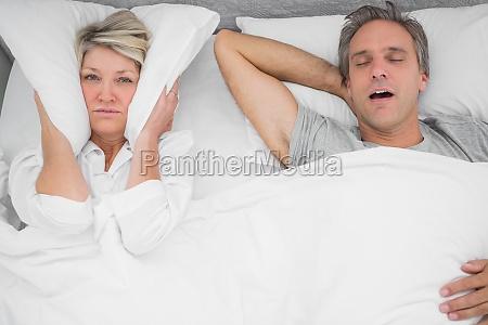 man snoring loudly as partner blocks