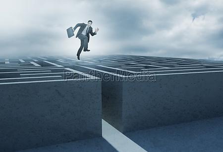 forretningsmand springer over en labyrint