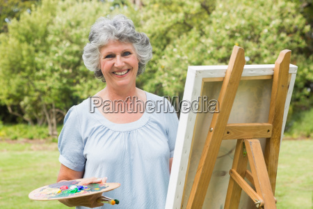 happy mature woman painting on canvas