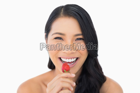 gorgeous brown haired model eating strawberry