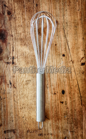 metal whisk on a wooden background