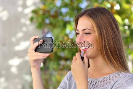 beautiful woman making up using a