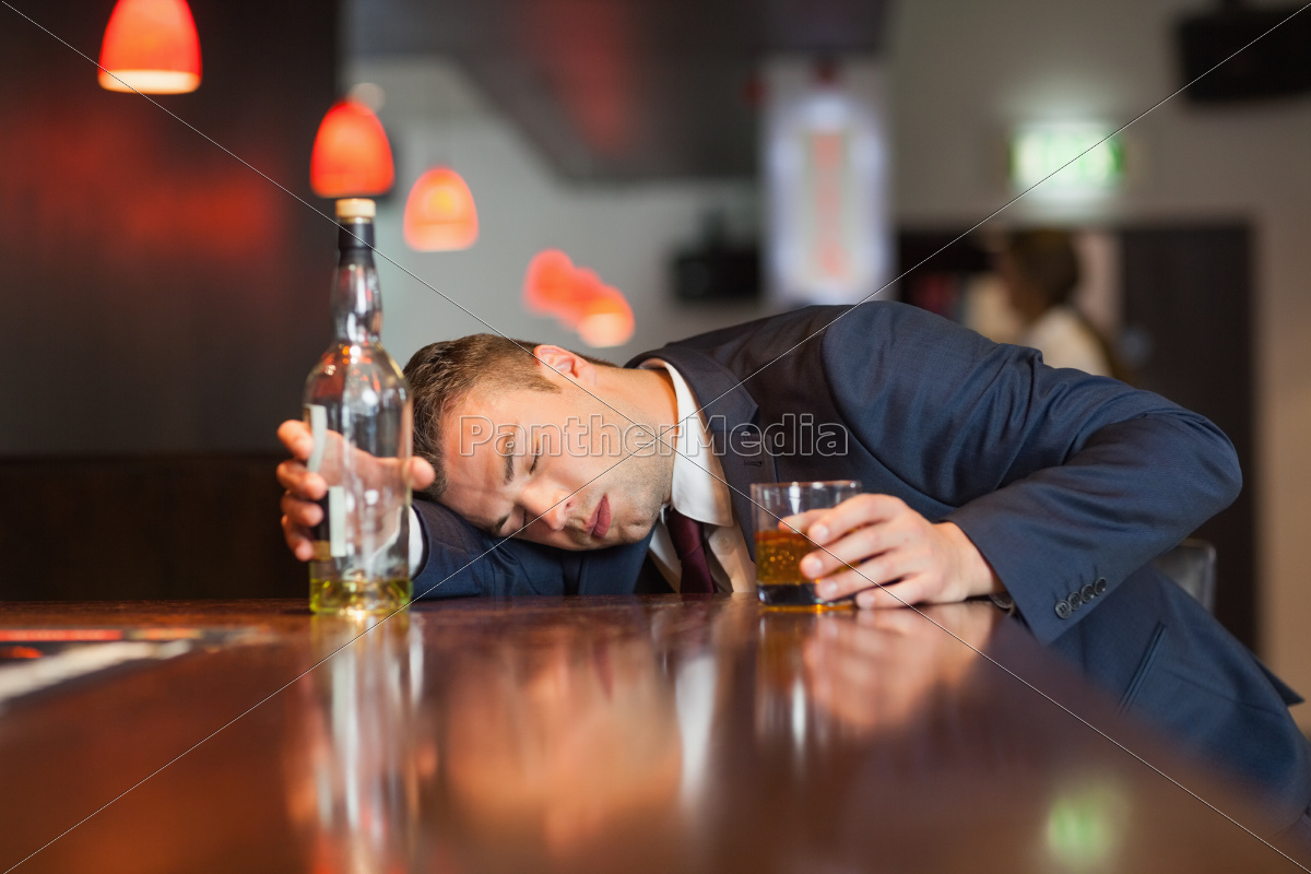 unmoving, businessman, holding, whiskey, glass, lying - 10073790