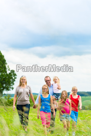 happy family running in a meadow
