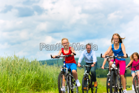 family riding bikes in the summer