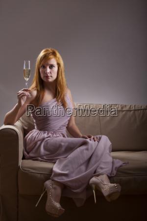 frau in einem abendkleid mit champagner