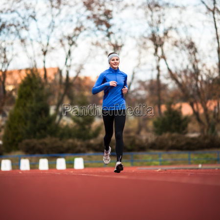 young, woman, running, at, a, track - 10147191