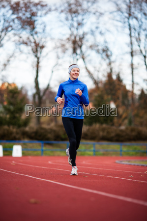 young, woman, running, at, a, track - 10147205