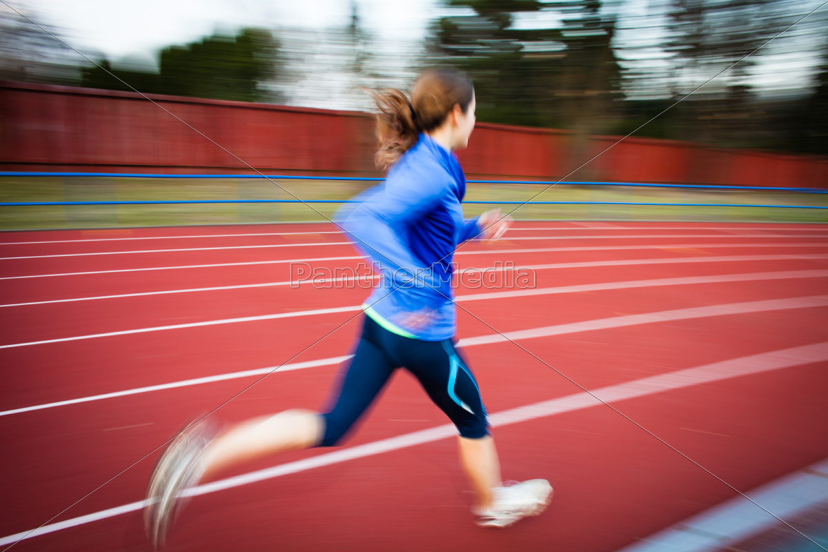 young, woman, running, at, a, track - 10147317