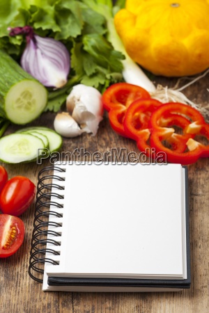 notebook with vegetables on wood