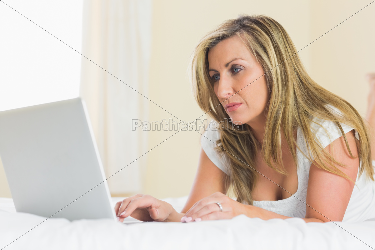 concentrated, woman, using, her, laptop, lying - 10209557