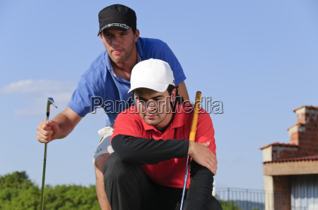 young golfers putting on the green