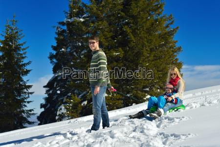 family having fun on fresh snow