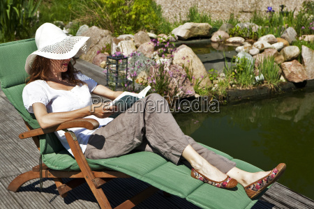 woman reads at the pond