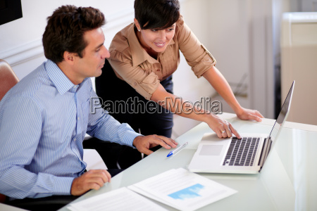 two professional colleagues looking at computer
