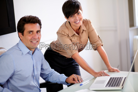 attractive professional couple smiling at you