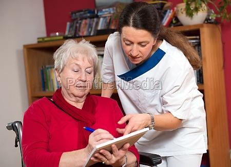 nurse helping senior citizen in a