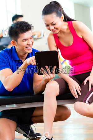 asian personal trainer with woman in