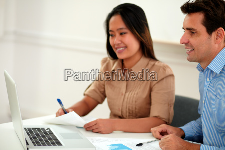 two multi ethnic colleagues working on
