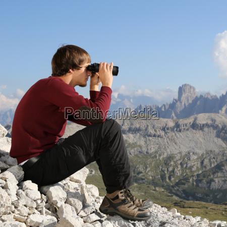 young man looks through binoculars in