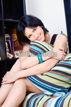 woman behind pillow at home