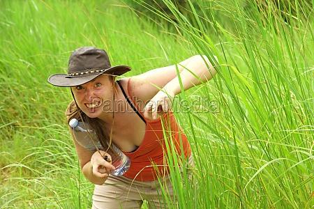 adventure woman hides in grass pretending