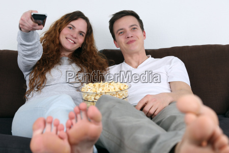 young couple watch tv and eat