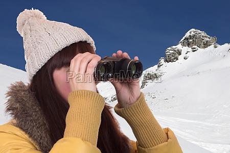 young woman looks through binoculars in