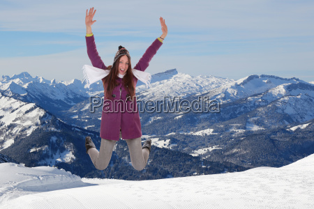 young woman jumps in the mountains