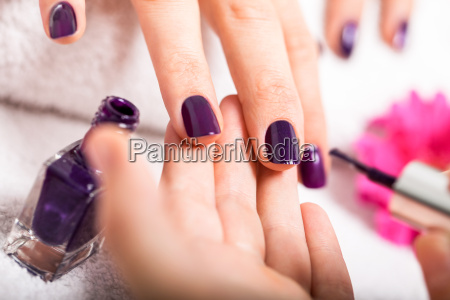 woman gets her nails in purple