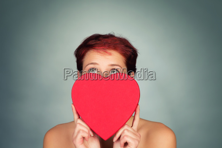 young woman behind a red heart