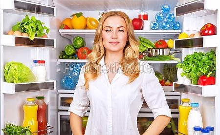 mulher saudavel perto do frigorifico aberta