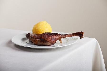 roast goose leg on linen tablecloth